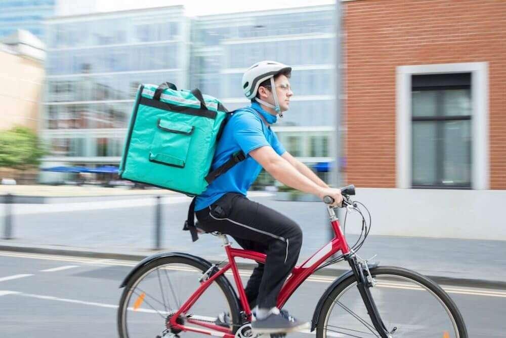 自転車に乗るウーバーイーツの配達員