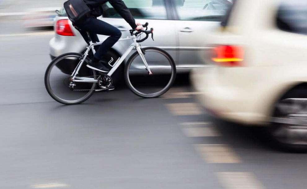 車の間を走る自転車のライダー