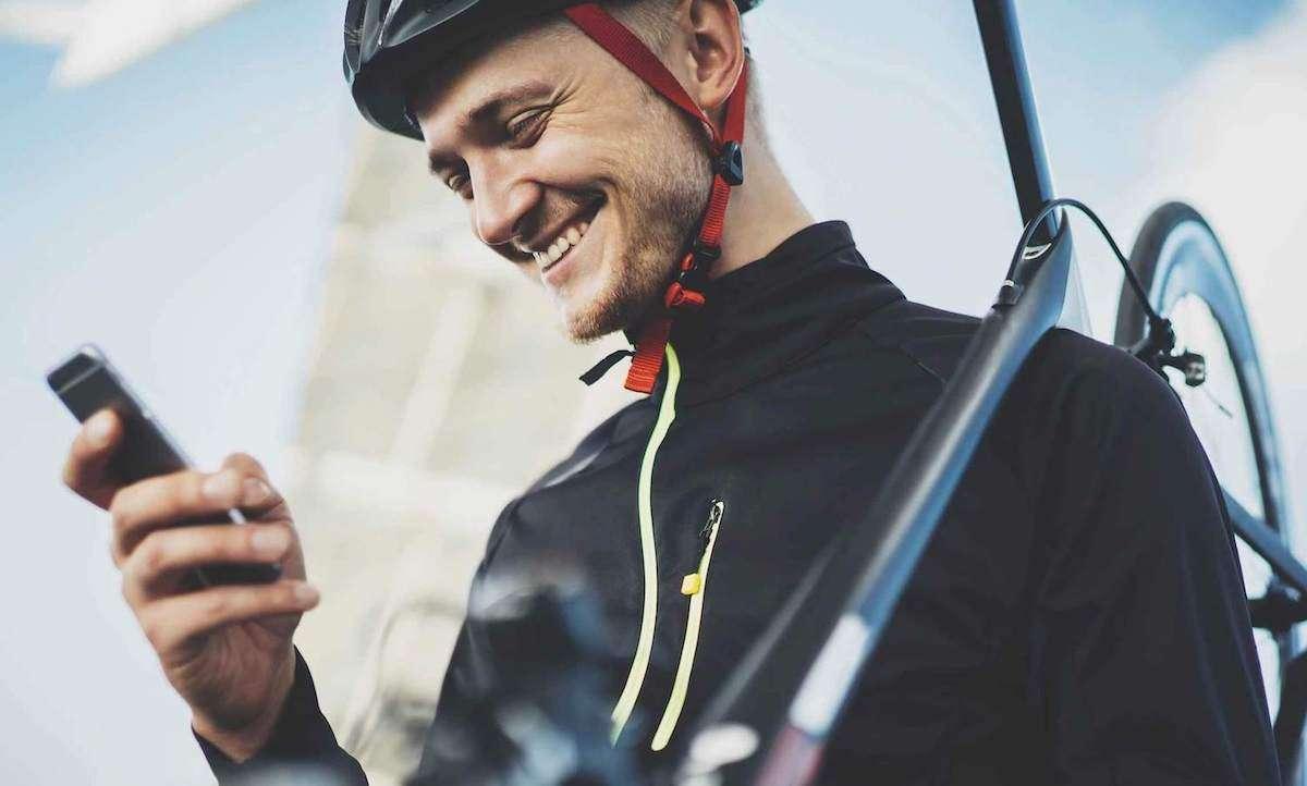 自転車を担いでスマホを見ながら微笑む男性